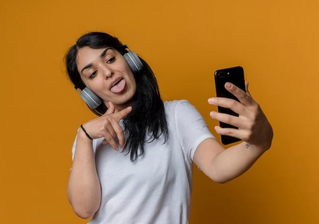 Joyeuse jeune fille brune caucasienne sur les écouteurs regarde et pointe le téléphone isolé sur le mur orange