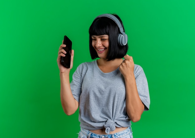 Joyeuse jeune fille caucasienne brune sur les écouteurs tient le téléphone et garde le poing