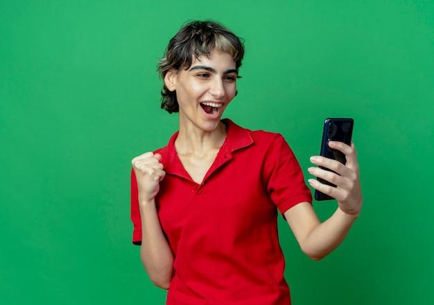 Joyeuse jeune fille caucasienne avec coupe de cheveux de lutin tenant et regardant un téléphone portable avec le poing fermé