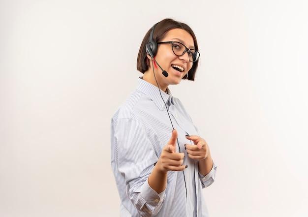 Joyeuse jeune fille de centre d'appels portant des lunettes et un casque debout en vue de profil vous faisant un geste à l'avant isolé sur blanc