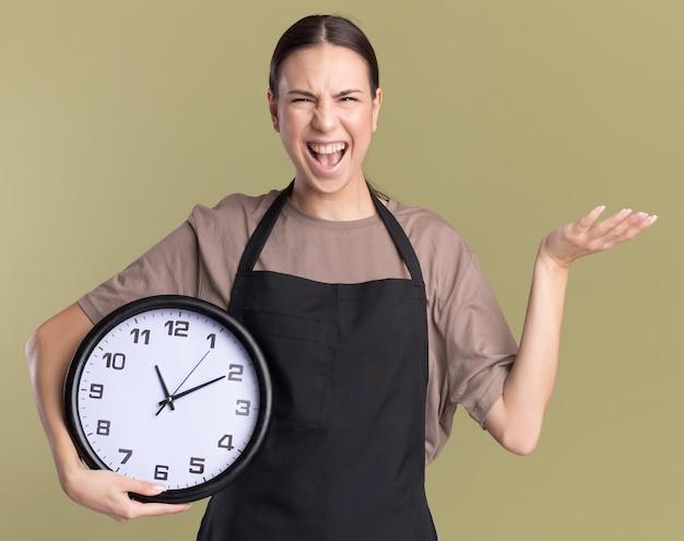 Joyeuse jeune fille de coiffeur brune en uniforme garde la main ouverte et tient horloge sur vert olive