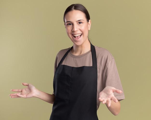 Joyeuse jeune fille de coiffeur brune en uniforme tient les mains ouvertes