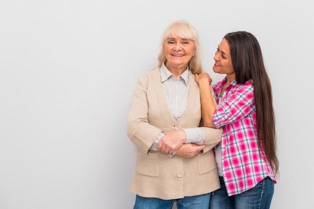 Joyeuse jeune fille debout avec sa mère sur fond blanc