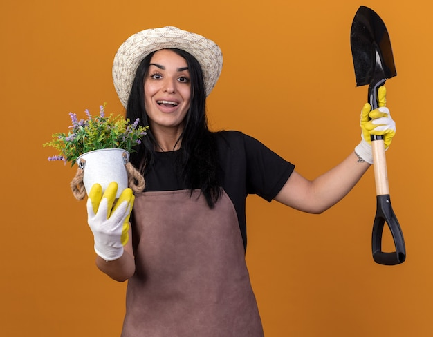 Joyeuse jeune fille de jardinier en uniforme et chapeau avec des gants de jardinier tenant une pelle et un pot de fleurs regardant à l'avant isolé sur un mur orange