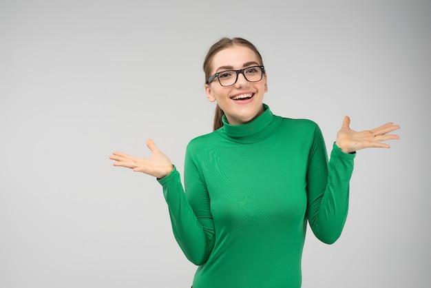 Joyeuse jeune fille qui pose en studio hausse les épaules avec surprise