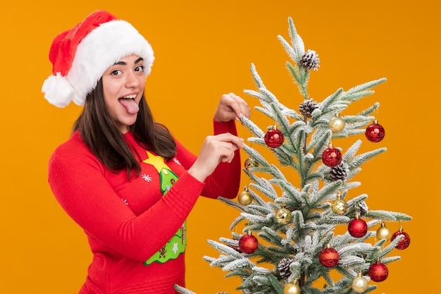 Joyeuse jeune fille de race blanche avec bonnet de noel sort la langue debout à côté de la décoration de l'arbre de noël avec des jouets isolés sur fond orange avec espace copie