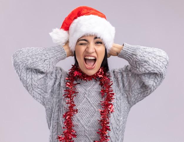 Joyeuse jeune fille de race blanche portant chapeau de noël et guirlande de guirlandes autour du cou en gardant les mains sur la tête en hurlant et en clignant de l'œil isolé sur un mur blanc