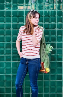 Joyeuse jeune fille de race blanche avec un sac en filet sur son épaule avec des légumes sur un mur vert dans la rue