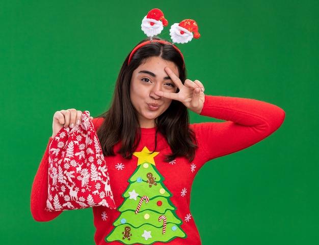 Joyeuse jeune fille de race blanche avec le signe de la victoire des gestes du bandeau de santa et tient le sac de cadeau de noël isolé sur fond vert avec espace de copie