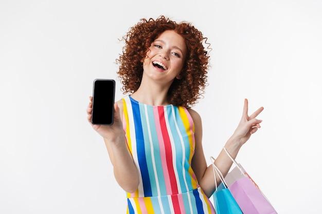 Joyeuse jeune fille rousse portant une robe, portant des sacs à provisions isolés sur un mur blanc, montrant un téléphone portable à écran blanc