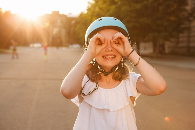 Joyeuse jeune fille s'amusant, regardant la caméra à travers des jumelles imaginaires