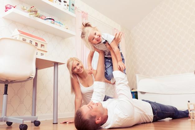 Joyeuse jeune fille s'amusant avec son père dans la chambre des enfants à la maison