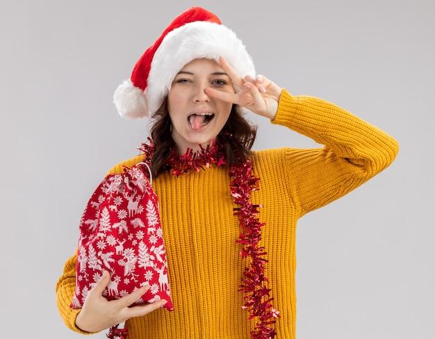 Joyeuse jeune fille slave avec bonnet de noel et avec guirlande autour du cou sort la langue et les gestes signe de victoire tenant le sac de cadeau de noël isolé sur fond blanc avec espace de copie