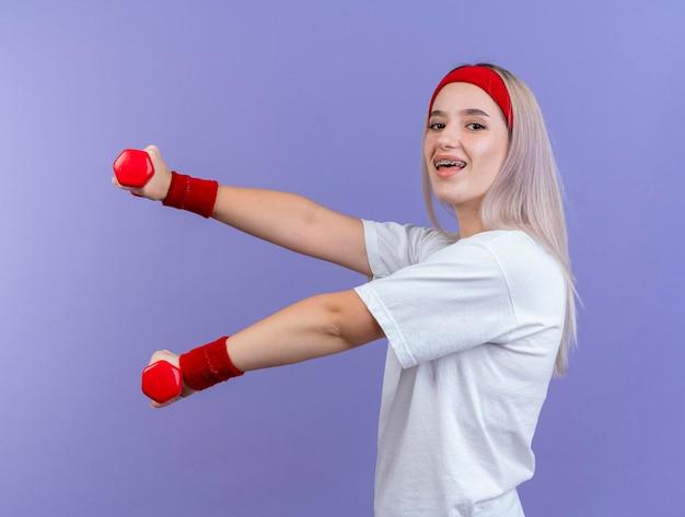 Joyeuse jeune fille sportive caucasienne avec des accolades portant bandeau