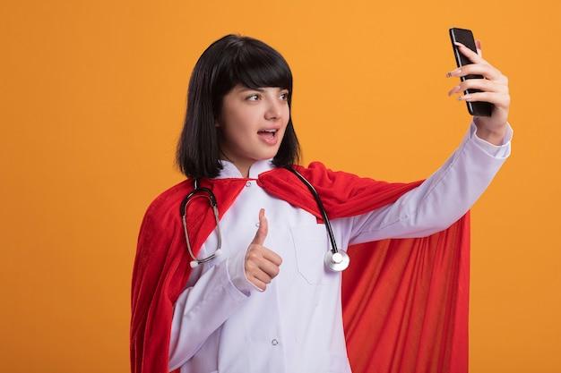 Joyeuse jeune fille de super-héros portant un stéthoscope avec une robe médicale et une cape prendre un pouce selfie isolé sur orange