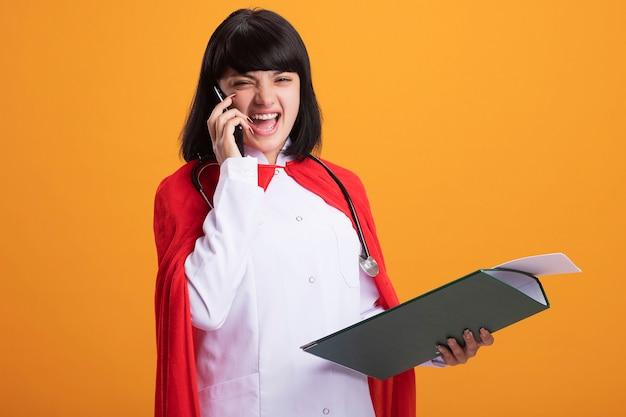 Joyeuse jeune fille de super-héros portant un stéthoscope avec une robe médicale et une cape tenant le presse-papiers parle au téléphone isolé sur un mur orange