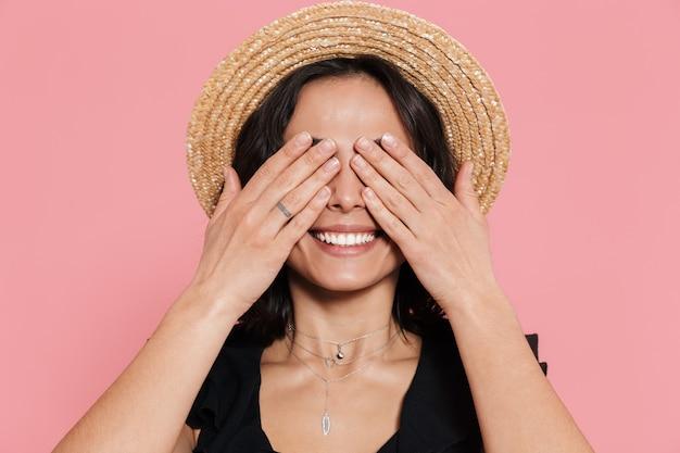 Joyeuse jeune fille vêtue d'une robe d'été isolée sur un mur rose