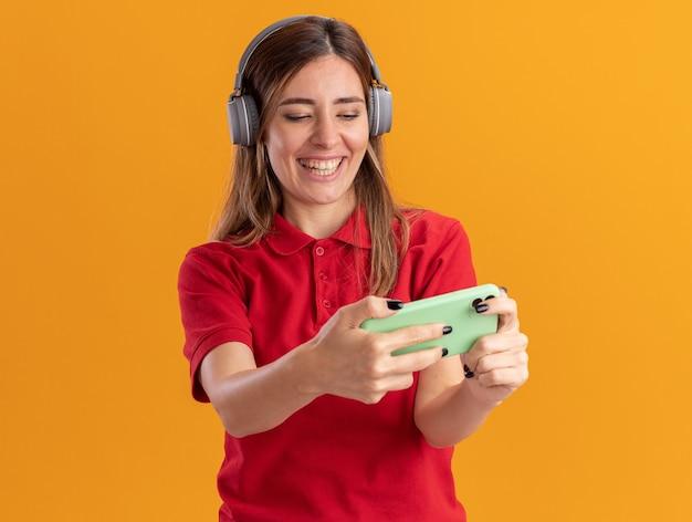 Joyeuse jeune jolie femme sur le casque tient et regarde le téléphone isolé sur le mur orange