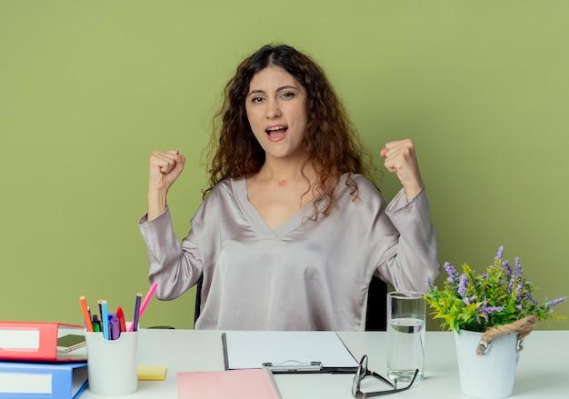 Joyeuse jeune jolie femme employé de bureau assis au bureau avec des outils de bureau montrant oui geste isolé sur fond d'olive