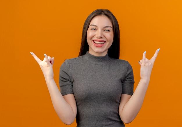 Joyeuse jeune jolie femme faisant des signes de roche isolés sur fond orange