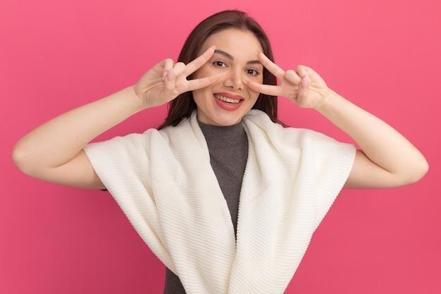 Joyeuse jeune jolie femme montrant des symboles de signe v près des yeux