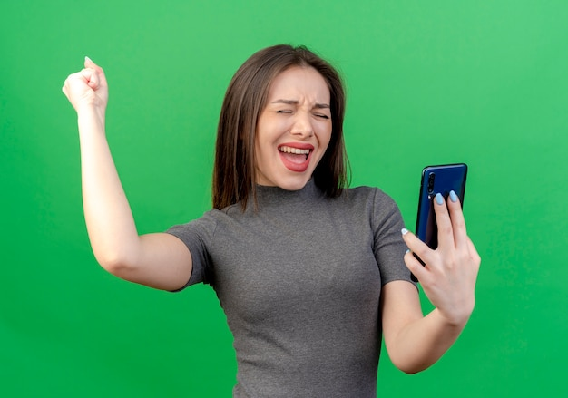 Joyeuse jeune jolie femme tenant un téléphone mobile en levant le poing faisant oui geste avec les yeux fermés isolé sur fond vert