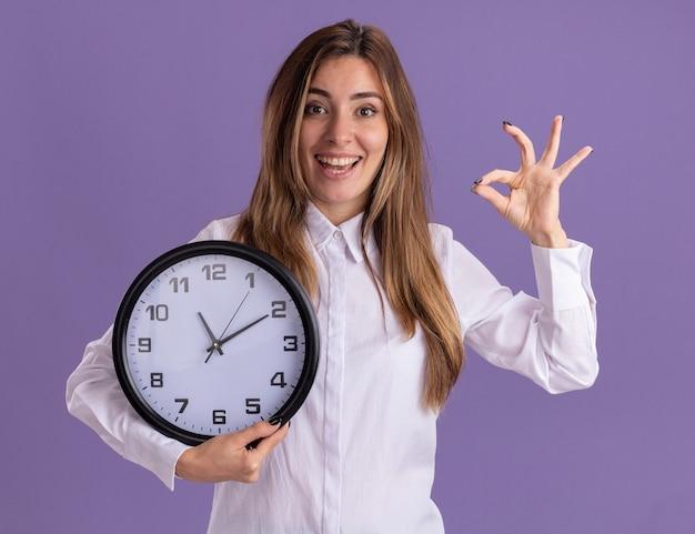 Joyeuse jeune jolie fille caucasienne fait des gestes ok signe de la main et tient l'horloge