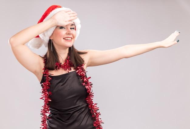 Joyeuse jeune jolie fille caucasienne portant un bonnet de noel et une guirlande de guirlandes autour du cou regardant la caméra faisant un geste de dab isolé sur fond blanc