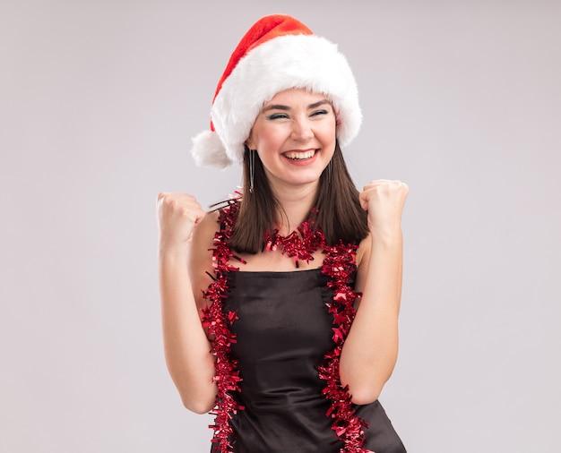 Joyeuse jeune jolie fille caucasienne portant un bonnet de noel et une guirlande de guirlandes autour du cou regardant de côté faisant un geste oui isolé sur fond blanc