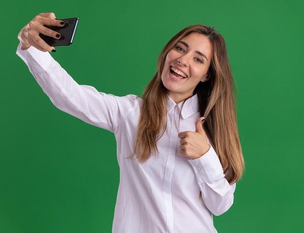 Joyeuse jeune jolie fille caucasienne pouces vers le haut et tient le téléphone isolé sur un mur vert avec espace de copie
