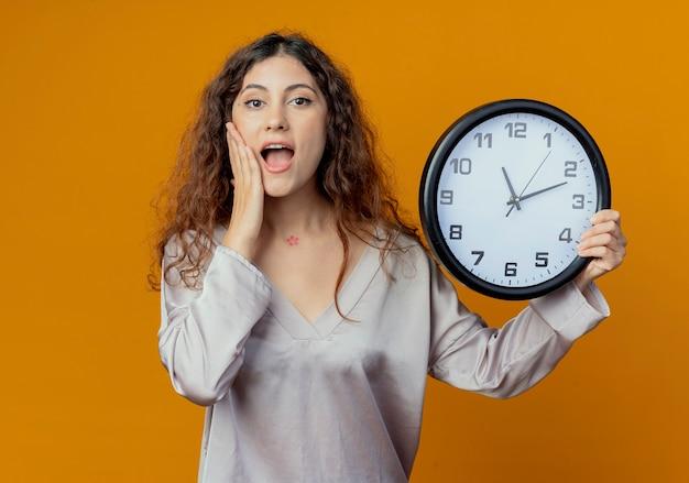 Joyeuse jeune jolie fille tenant une horloge murale et mettant la main sur la joue