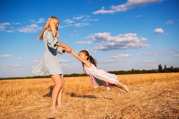 Joyeuse jeune mère fait tourner sa jolie petite fille