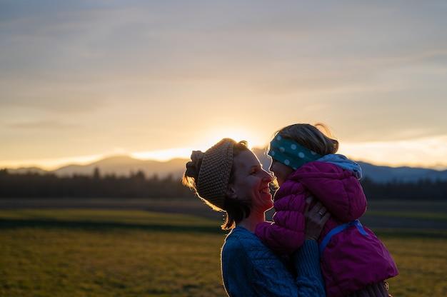 Joyeuse jeune mère souriante soulevant sa petite fille à l'extérieur dans une belle prairie au coucher du soleil.