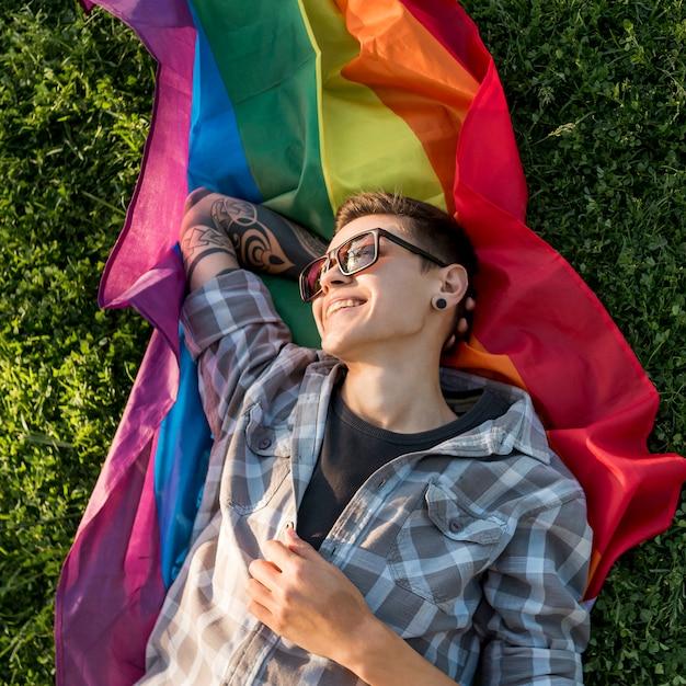 Joyeuse jeune personne allongée sur le drapeau lgbt dans le parc