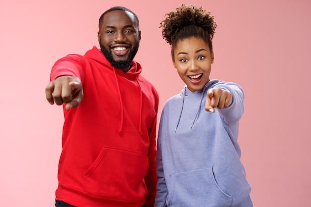 Joyeuse jeune séduisante heureuse couple afro-américain vacances profitant d'une visite intéressante debout impressionné étonné fond rose pointant l'index appareil photo génial objet curieux