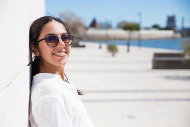 Joyeuse jeune touriste profitant de vacances au bord de mer