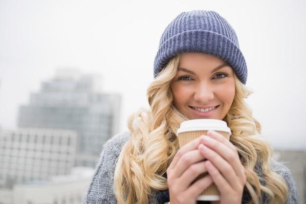 Joyeuse jolie blonde ayant du café à l'extérieur