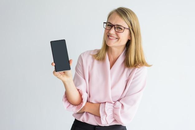 Joyeuse jolie dame appréciant d'utiliser smatphone moderne et montrant gadget
