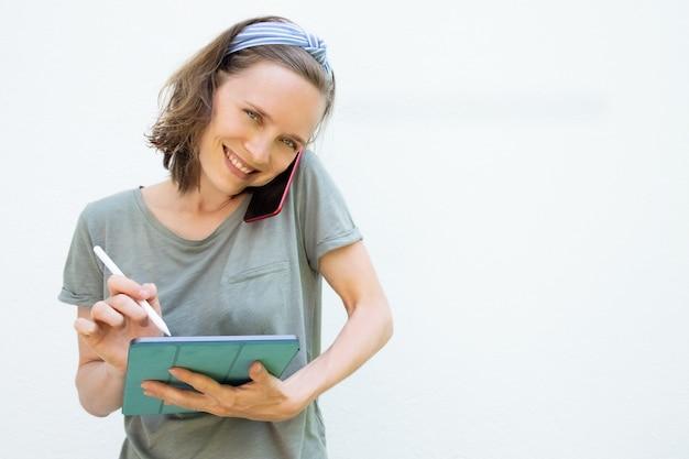 Joyeuse jolie femme à l'aide d'une tablette et d'un stylo