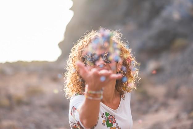 Joyeuse jolie femme caucasienne bouclée lance des confettis pour profiter de la vie et des vibrations positives se sentant en plein air - concept de célébration de carnaval pour les gens joyeux