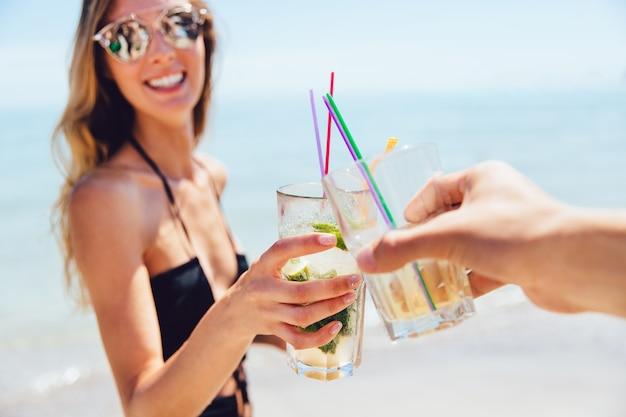 Joyeuse jolie femme en lunettes de soleil boire un cocktail avec un ami, grillage