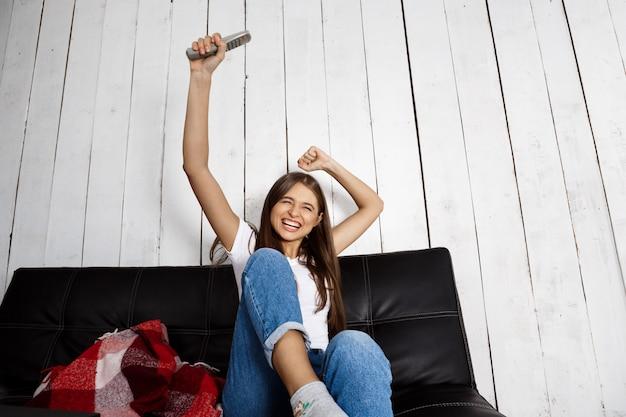 Joyeuse jolie femme regardant la télévision, assise sur le canapé à la maison.