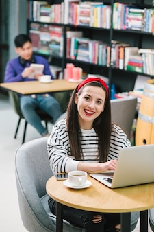 Joyeuse jolie femme souriante assise avec un ordinateur portable et une tasse de café dans une bibliothèque confortable