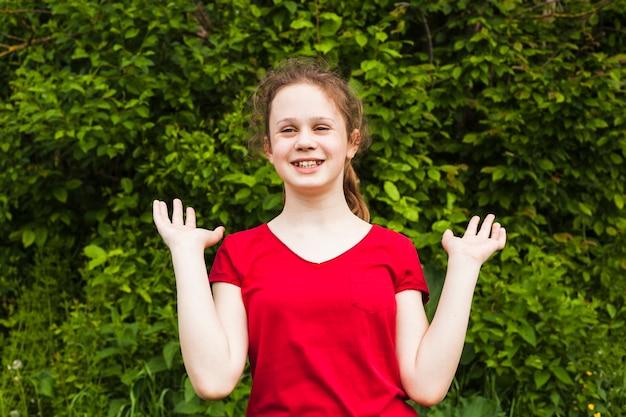 Joyeuse jolie fille debout dans le parc et gesticulant