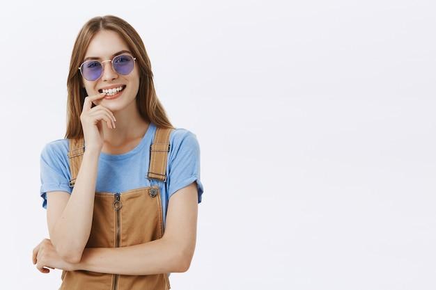 Joyeuse jolie fille heureuse à lunettes de soleil en riant et souriant sans soucis