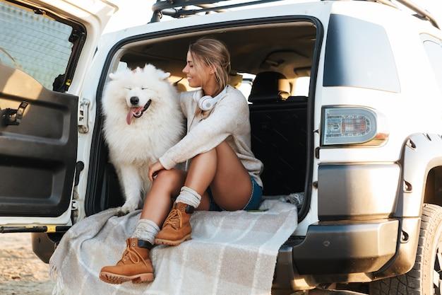 Joyeuse jolie fille jouant avec son chien assis dans une voiture à la plage