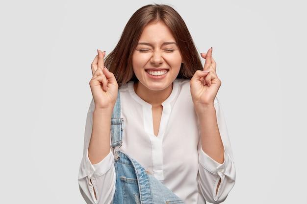 Joyeuse jolie fille souriante avec une expression heureuse, lève les doigts croisés, fait voeu