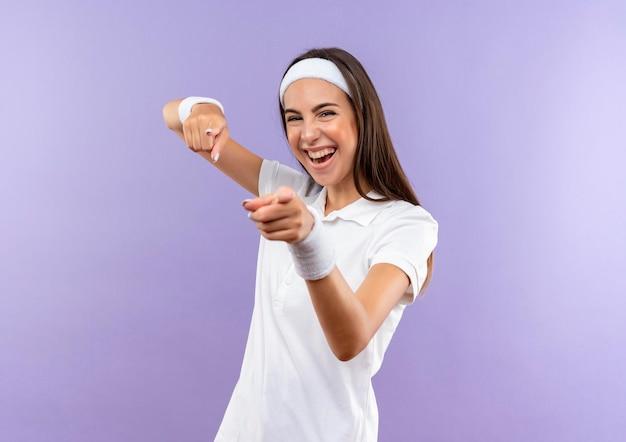 Joyeuse jolie fille sportive portant un bandeau et un bracelet vous faisant un geste isolé sur un mur violet