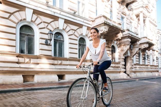 Joyeuse jolie fille sur le vélo à l'extérieur dans la ville