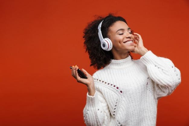 Joyeuse jolie jeune femme africaine portant des écouteurs sans fil debout isolé sur un mur rouge, tenant un téléphone portable, dansant